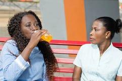 Jeune femme buvant la boisson et observée par son amie Photo libre de droits