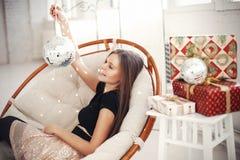 Jeune femme célébrant le réveillon de Noël avec les cadeaux actuels Photographie stock libre de droits