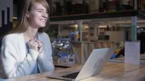 Jeune femme célébrant le succès, se reposant en café photo libre de droits