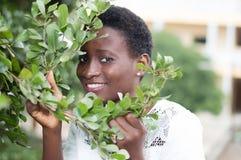 Jeune femme cachée derrière le feuillage Images libres de droits