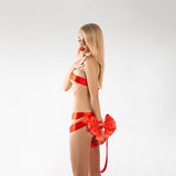 Jeune femme-cadeau mignon avec les rubans rouges sur le corps mince sexuel Image libre de droits