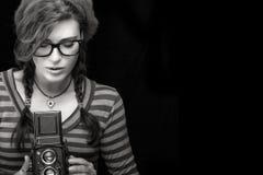 Jeune femme capturant la photo utilisant l'appareil-photo de vintage Por monochrome Image stock