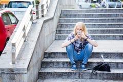 Jeune femme caucasienne à l'aide du téléphone intelligent tout en se reposant sur des escaliers Photographie stock