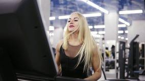 Jeune femme caucasienne attirante avec les cheveux blonds dans l'équipement noir de sport fonctionnant sur le treadmil au gymnase banque de vidéos