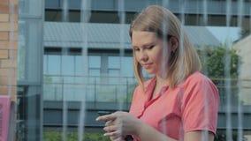 Jeune femme caucasienne attirante marchant aux rues ensoleillées de ville et causant avec des amis, utilisation joyeuse de fille banque de vidéos