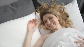 Jeune femme caucasienne attirante se réveillant pendant le début de la matinée, puis se trouvant et s'étirant banque de vidéos