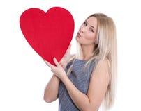 Jeune femme caucasienne blonde heureuse d'isolement tenant le grand coeur rouge Photographie stock