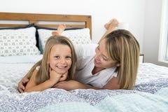 Jeune femme caucasienne blonde se trouvant sur le lit ainsi que ses jeunes 7 années douces et adorables de la fille à la maison b Image stock