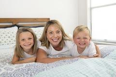 Jeune femme caucasienne blonde se trouvant sur le lit ainsi que ses petites sourire années de fils du bonbon 3 et 7 et de fille e photographie stock libre de droits