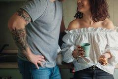 Jeune femme caucasienne bouclée souriant à son homme avec les tattoes et le thé potable photo stock