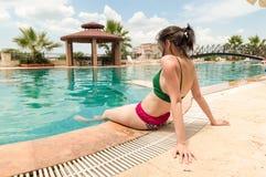 Jeune femme caucasienne détendant près de la piscine dans une station de vacances image stock