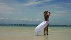 Jeune femme caucasienne dans la jupe blanche marchant sur Sandy Beach tropical banque de vidéos