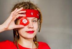 Jeune femme caucasienne de hippie avec les dreadlocks et le bandeau rouge couvrant son oeil de coeur d'origami Photo libre de droits