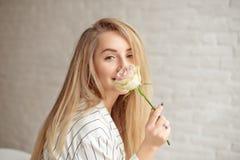 Jeune femme caucasienne en gros plan tenant le bouquet des fleurs, regards par la fenêtre avec le sourire heureux sur le visage s image stock