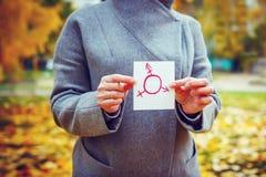 Jeune femme caucasienne en parc d'automne montrant le morceau de papier avec le symbole de transsexuel dessiné dans lui Concept d Photos libres de droits