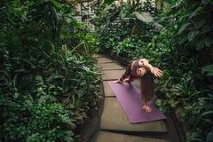 Jeune femme caucasienne faisant le yoga étirant des exercices au jardin botanique Photographie stock libre de droits
