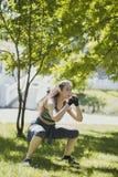 Jeune femme caucasienne faisant reposer-UPS s'exerçant en parc au jour ensoleillé Photo stock