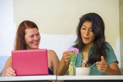 Jeune femme caucasienne heureuse et belle fille hispanique travaillant au caf? de bureau avec l'ordinateur portable discutant en  images stock
