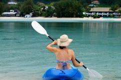 Jeune femme caucasienne kayaking au-dessus de l'eau de turquoise Photographie stock libre de droits