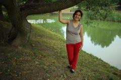 Jeune femme caucasienne sous l'arbre près du lac Photos stock