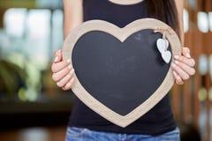 Jeune femme caucasienne tenant le tableau noir sous la forme de coeur Photographie stock