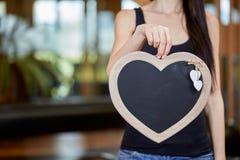 Jeune femme caucasienne tenant le tableau noir sous la forme de coeur Image stock