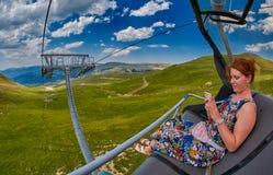 Jeune femme causant avec des amis montant le ropeway en montagnes Photos libres de droits