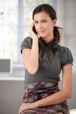 Jeune femme causant sur le mobile à la maison Image libre de droits