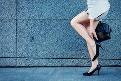 Jeune femme cessée pour vérifier ses talons Images stock