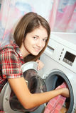 Jeune femme chargeant la machine à laver photographie stock libre de droits