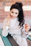 Jeune femme charismatique avec la queue de poney onduleuse foncée ayant mani rouge photo libre de droits