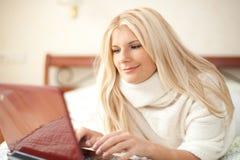 Jeune femme chating en ligne avec l'ordinateur portatif sur son bâti Photographie stock libre de droits