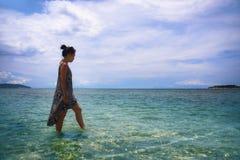Jeune femme chinoise asiatique décontractée marchant sur la plage d'île de la Thaïlande avec de l'eau beau étonnant couleur de tu Photographie stock