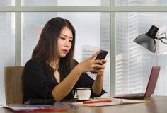 Jeune femme chinoise asiatique heureuse et belle d'entrepreneur travaillant au bureau moderne d'ordinateur de bureau au district  photos libres de droits