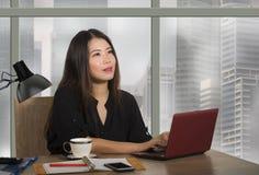 Jeune femme chinoise asiatique heureuse et belle d'entrepreneur travaillant au bureau moderne d'ordinateur de bureau au district  photos stock
