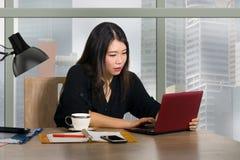 Jeune femme chinoise asiatique heureuse et belle d'entrepreneur travaillant au bureau moderne d'ordinateur de bureau au district  photographie stock libre de droits