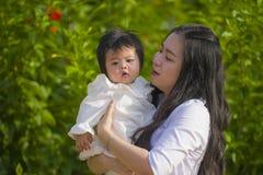 Jeune femme chinoise asiatique heureuse et mignonne appréciant et jouant avec sa fille de bébé jugeant son sourire gai au jardin images stock
