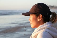 Jeune femme chinoise en bonne santé regardant le coucher du soleil sur la plage photos stock