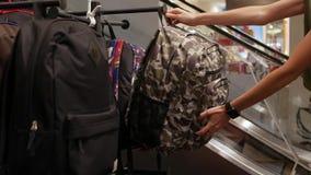 Jeune femme choisissant dans le magasin un sac à dos La fille dans un supermarché achète un sac Concept d'escompte 4K banque de vidéos