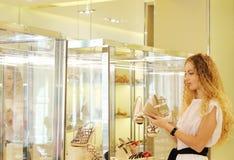 Jeune femme choisissant des chaussures à une mémoire photos stock
