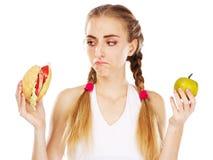 Jeune femme choisissant entre l'hamburger et la pomme Image libre de droits