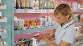 Jeune femme choisissant la crème cosmétique dans la boutique de beauté Images stock
