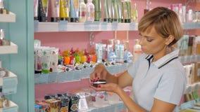Jeune femme choisissant la crème cosmétique dans la boutique de beauté Photo libre de droits