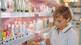 Jeune femme choisissant la crème cosmétique dans la boutique de beauté Image stock