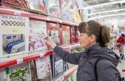 Jeune femme choisissant la literie Images stock