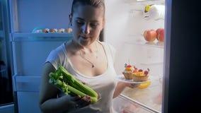 Jeune femme choisissant la nourriture saine au lieu des bonbons Concept de la nutrition et de suivre un régime sains banque de vidéos