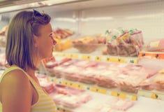 Jeune femme choisissant la viande Images libres de droits