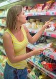 Jeune femme choisissant la viande Images stock