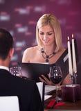 Jeune femme choisissant le menu Image stock