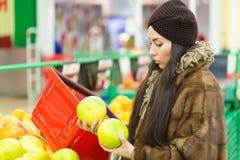 Jeune femme choisissant le pamplemousse d'orange ou de pamplemousse pendant les achats au supermarché images libres de droits